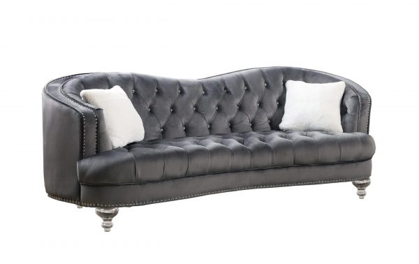 Upholstered camelback style sofa tufted with faux crystals in velvet fabric with acrylic legs.