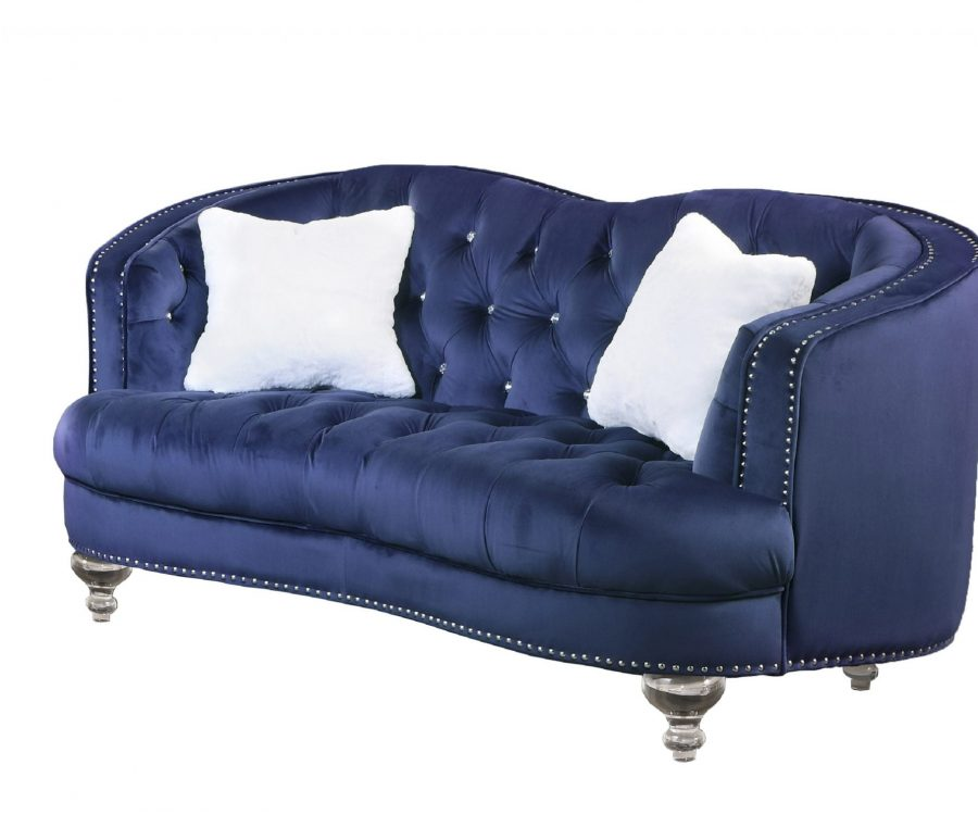 Upholstered camelback style loveseat tufted with faux crystals in velvet fabric with acrylic legs.